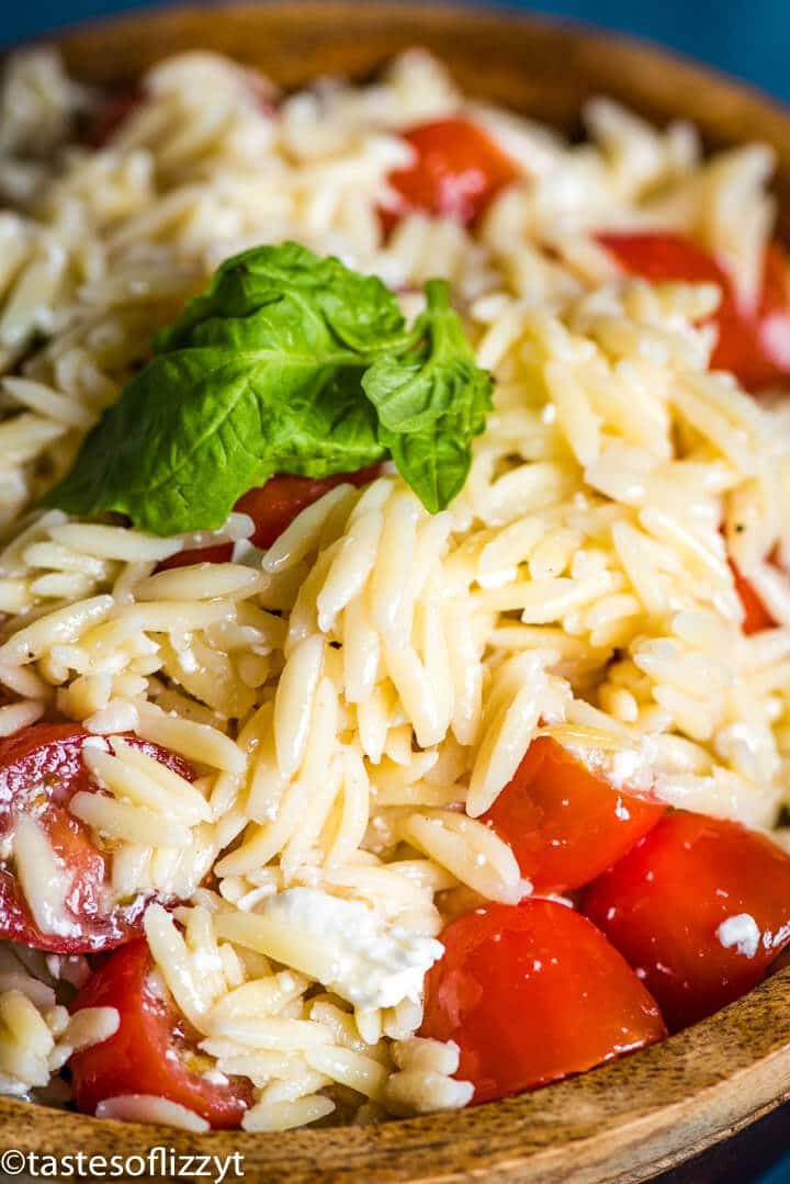 A close up of a bowl of orzo with feta and tomatoes