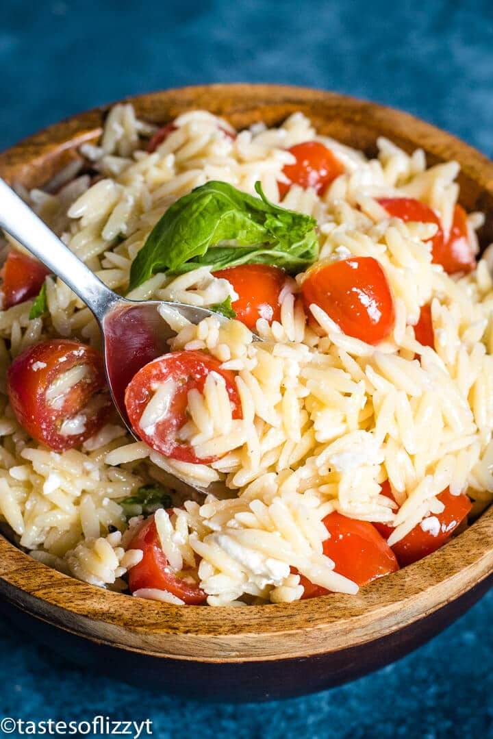 A bowl of food, with tomatoes and Orzo