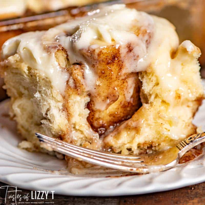 cinnamon roll on a plate with a fork