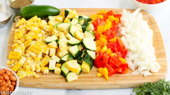 A bunch of food is on a cutting board, with Summer squash