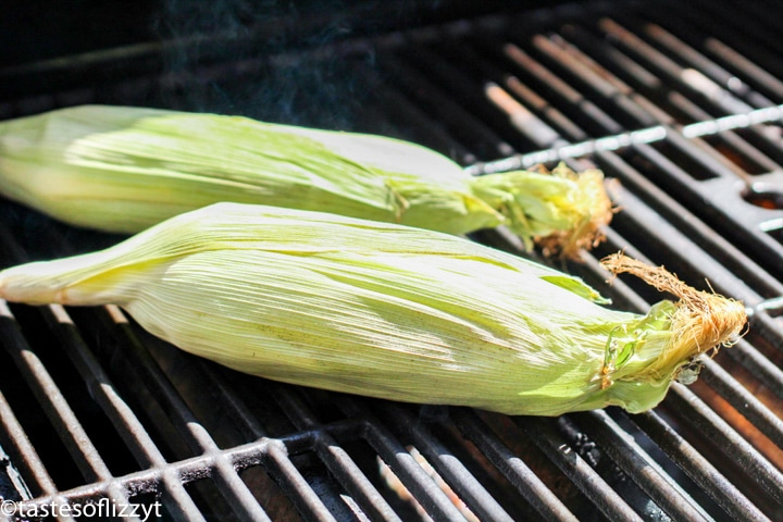 A close up of food on a grill, with Husk and Corn on the cob