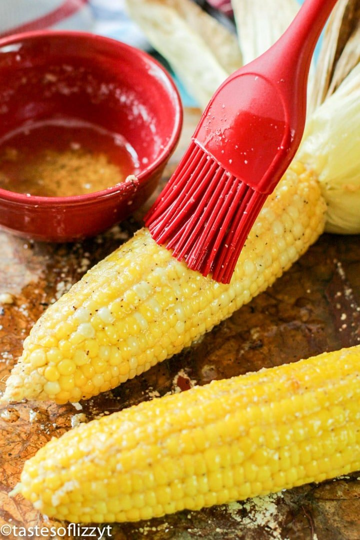 brushing butter on corn on the cob