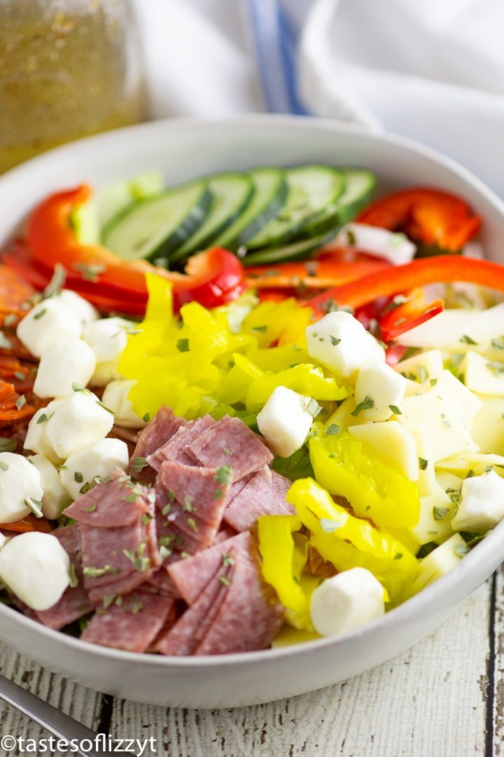 a bowl of salad with cucumbers, peppers and meat