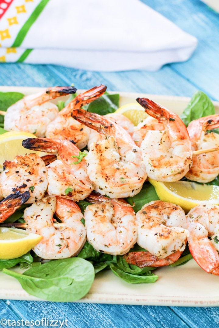 A plate of shrimp and vegetables, with Lemon and Skewer