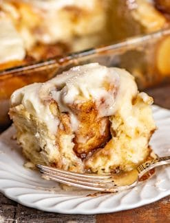 cinnamon roll on a plate with a bite out
