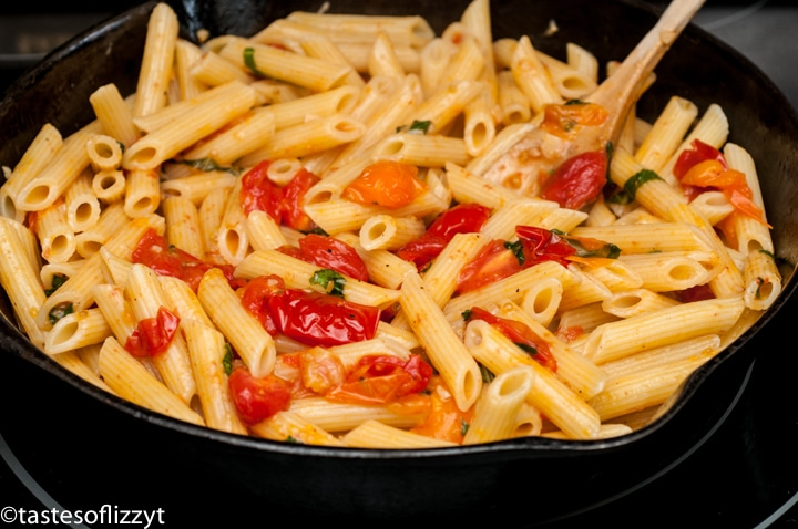 A bowl filled with pasta and vegetables, with Tomato and Basil