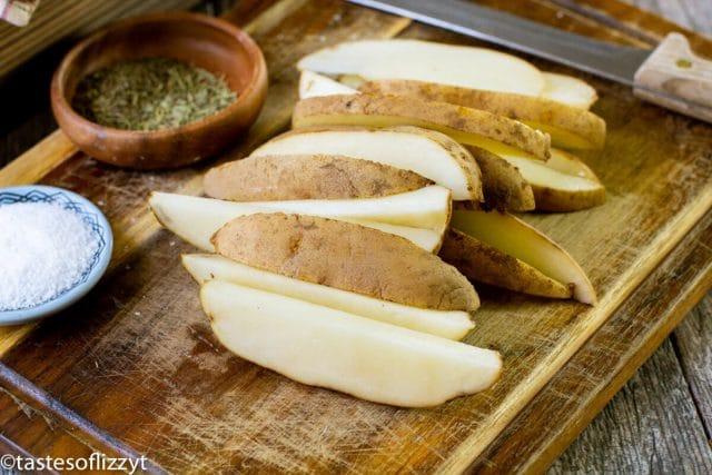 cut potato wedges on a cutting board