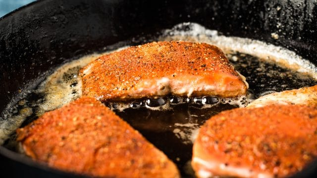 A close up of a piece of salmon frying in skillet