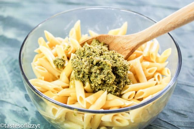 mixing penne and pesto in a bowl