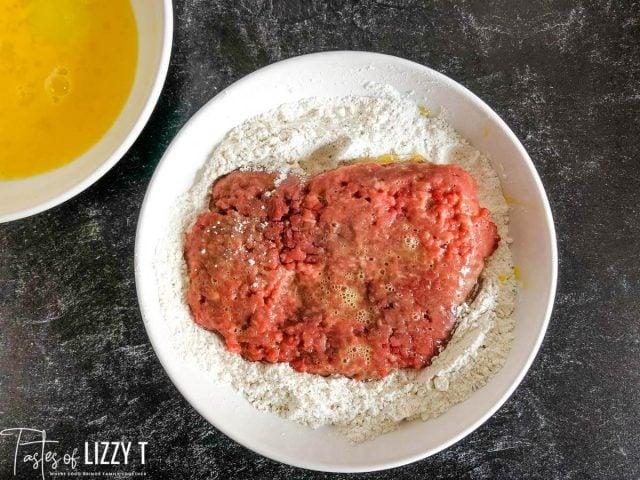 cube steak in a bowl of flour