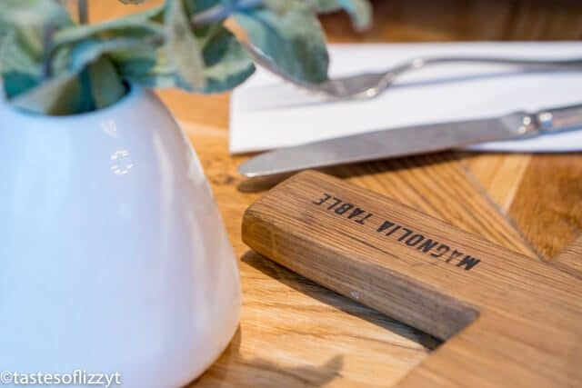 A knife sitting on top of a wooden cutting board, with Waco and Family