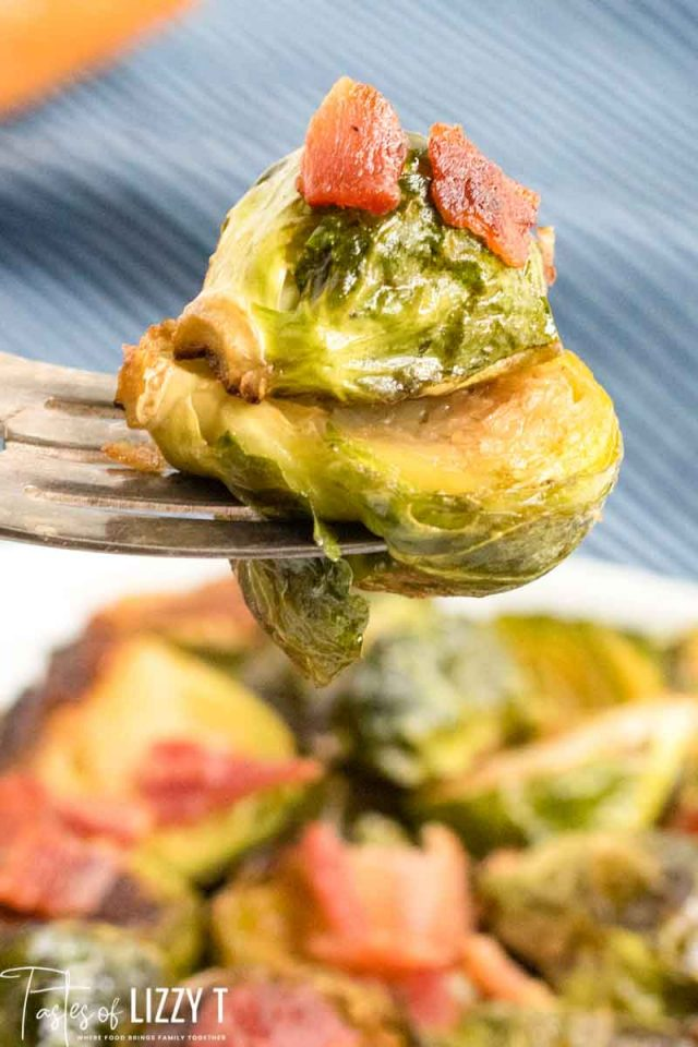 A close up of a plate of food, with Brussels sprouts on a fork