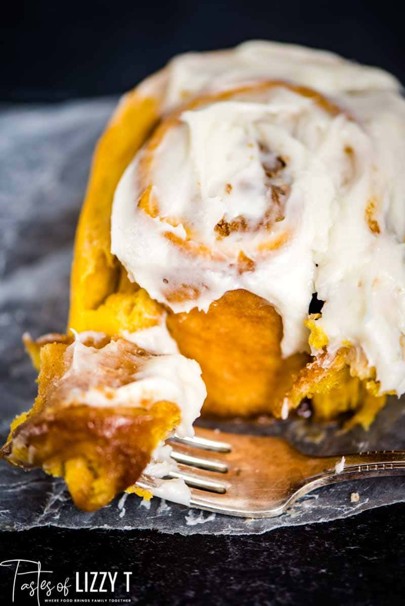 closeup of cinnamon roll and a fork with a bite