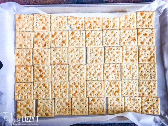 saltine crackers laid out on a baking sheet