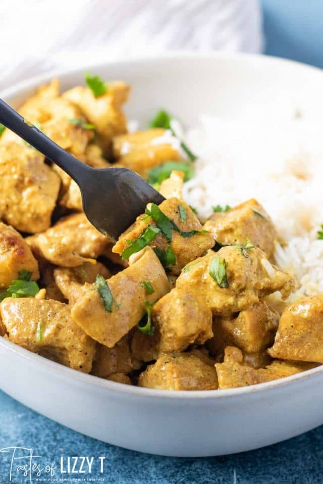 A bowl of food on a plate, with Curry and Chicken