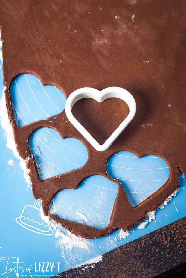 rolled out chocolate sugar cookie dough with heart cutouts