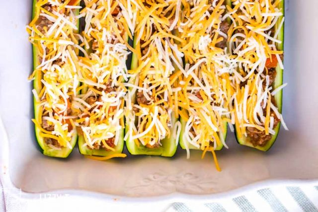 unbaked zucchini boats with shredded cheese on top