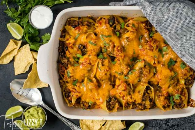 overhead shot of stuffed shells casserole with tortilla chips and garnishes