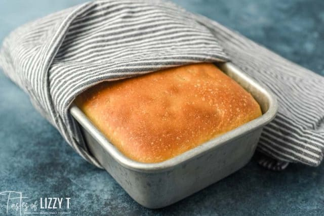 golden brown white bread in a loaf pan wrapped in a towel