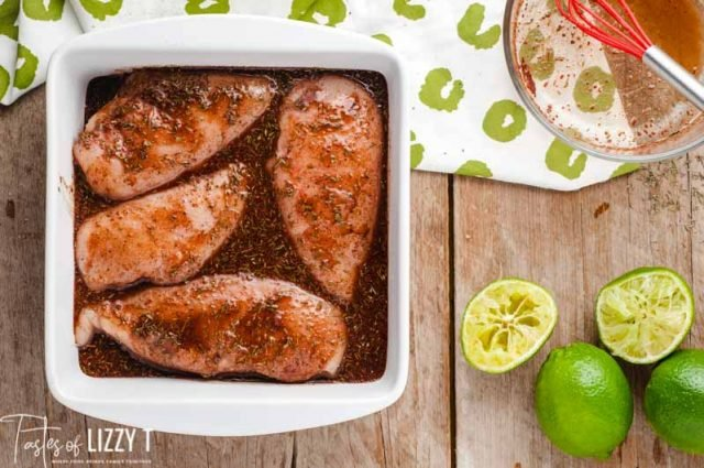 chicken marinating in a dish with limes
