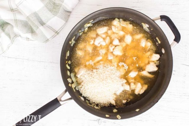 chicken broth, chicken and rice in a skillet
