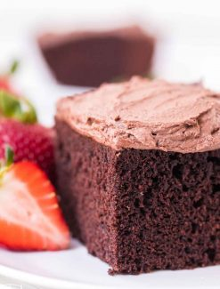 frosted chocolate cake on a plate with strawberries