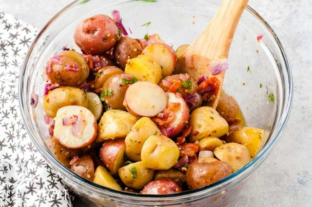warm potato salad in mixing bowl with wooden spoon