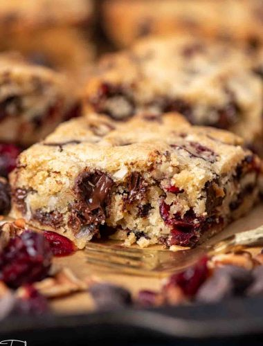 chocolate chunk cranberry coconut bars with a bite out of it