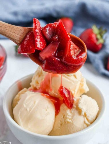 strawberry sauce pouring over ice cream