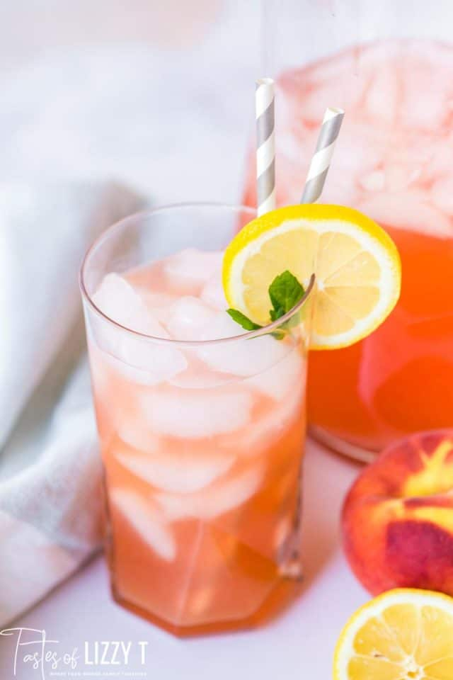a glass of homemade peach lemonade with two straws and a slice of lemon