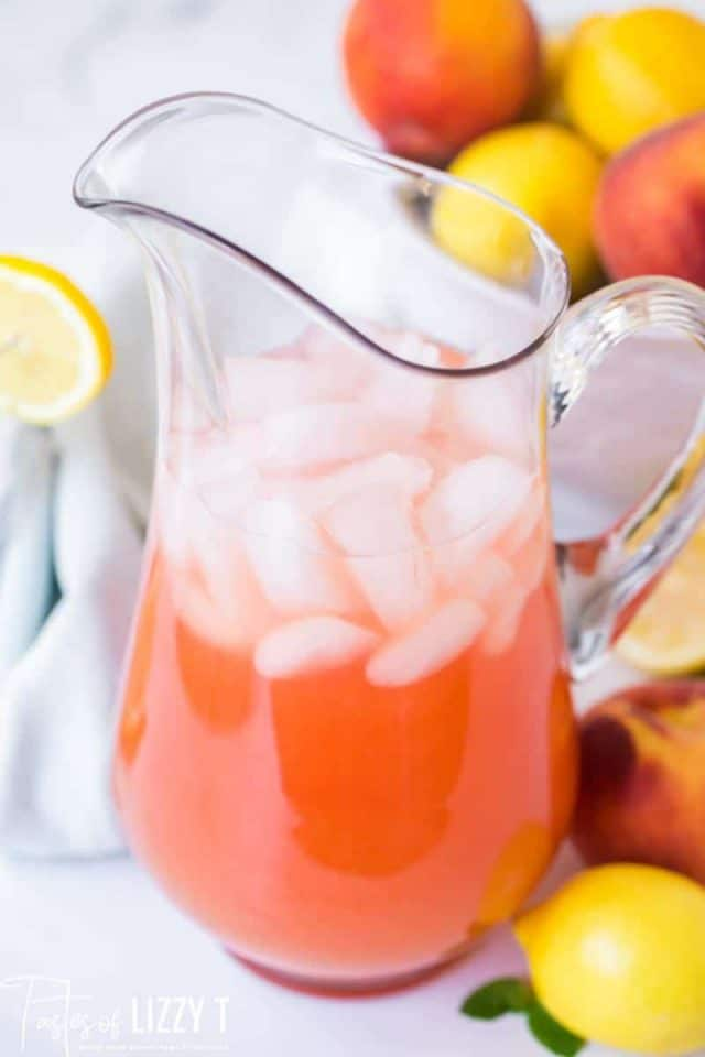 a pitcher of peach lemonade with ice