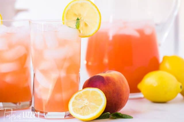 two glasses of peach lemonade with fresh peaches and lemons