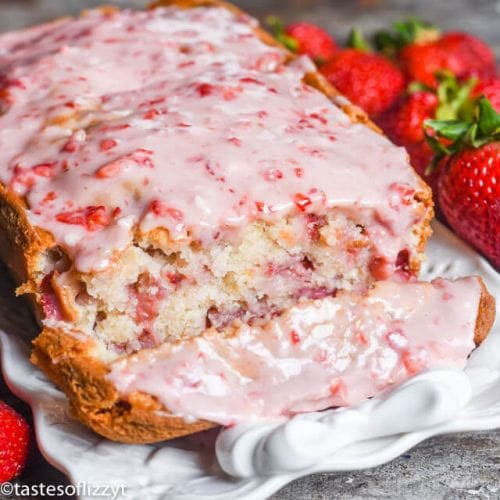 loaf of glazed strawberry bread with one slice cut