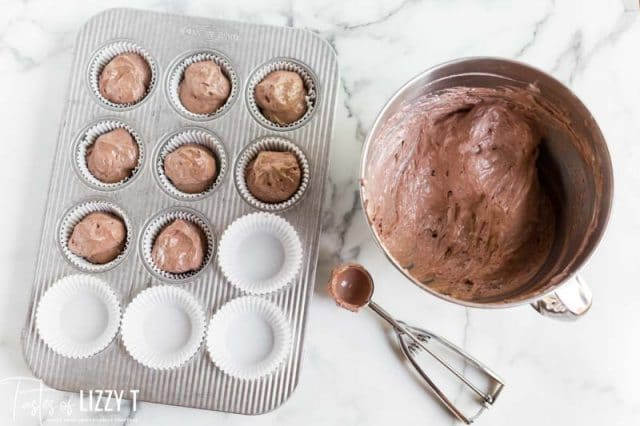 scooping cupcake batter into a pan