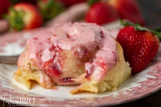 strawberries and cream sweet roll on a plate with a bite out of it