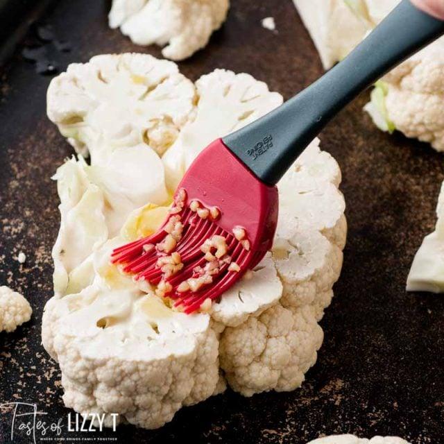 brushing olive oil over a cauliflower steak