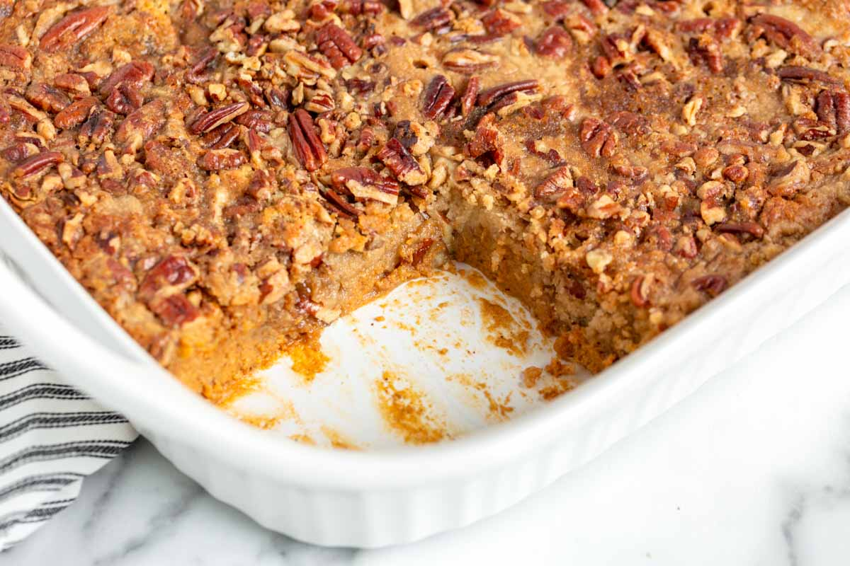 pecan pumpkin dump cake in a pan with one slice out