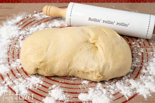 ball of dough and rolling pin on floured mat