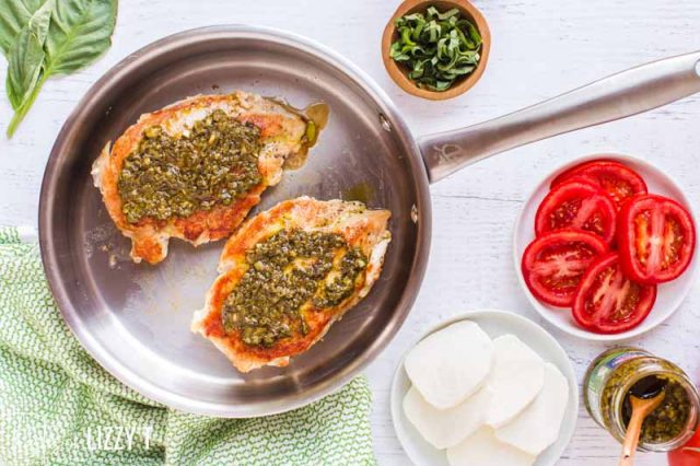 chicken in a skillet with pesto