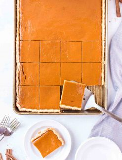 overhead view of pumpkin slab pie with one piece on plate