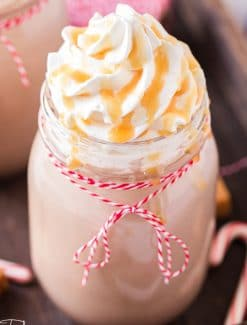 closeup of glass of caramel hot chocolate with whipped cream