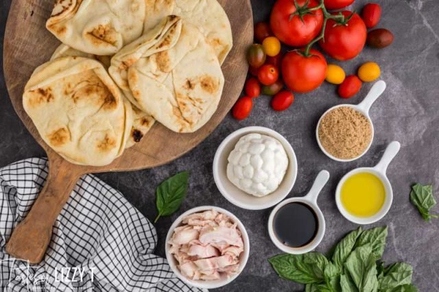 ingredients for chicken caprese pizzas on a table