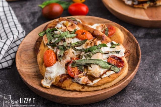 chicken tomato basil pizza on a wooden plate