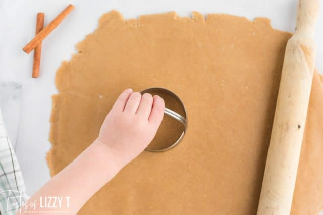 hand using a cookie cutter on rolled dough