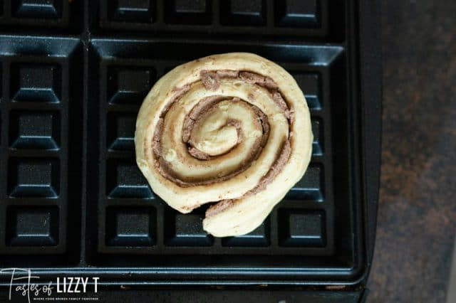 an uncooked cinnamon roll on a waffle iron
