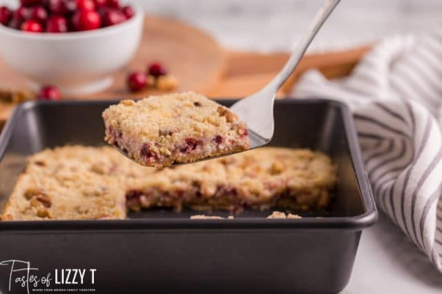 cranberry cream cheese bars in a pan on a spatula