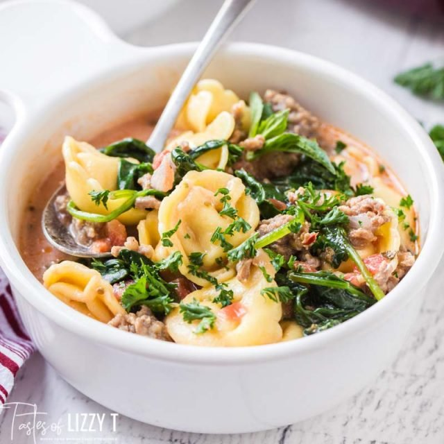 closeup of bowl of tortellini soup with spinach