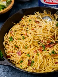 pasta carbonara in a skillet with a serving spoon