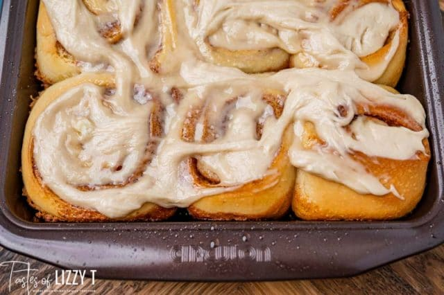 frosted cinnamon rolls in a baking pan