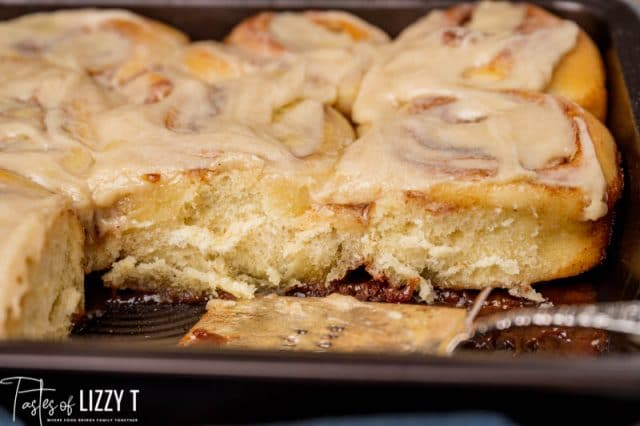 cinnamon rolls in a pan with two missing